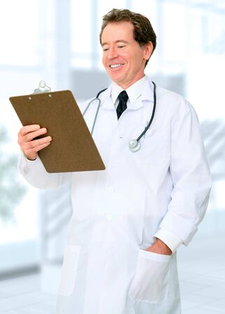 happy senior caucasian doctor reading report in hospital area photo