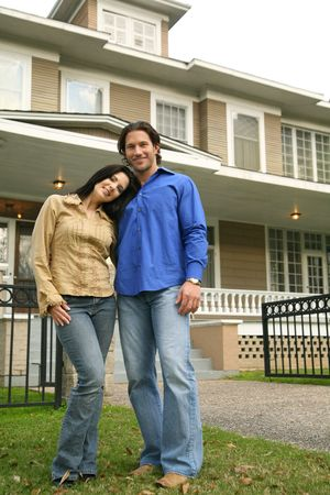 young caucasian couple smiling with their new house on the background Archivio Fotografico