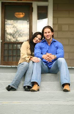 live happy: two people sit in front of their new house with happy expression