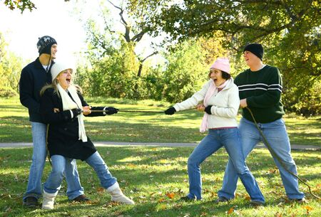 four friends in urban style playing tug of war in park photo