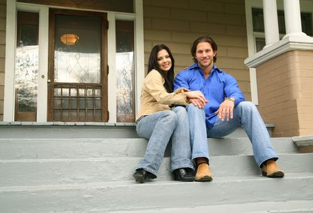 young couple with their new house. smiling and looking to camera Archivio Fotografico