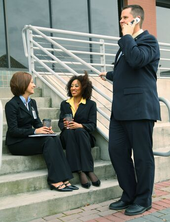 group of business people, caucasian and african american are talking outdoor by stair photo