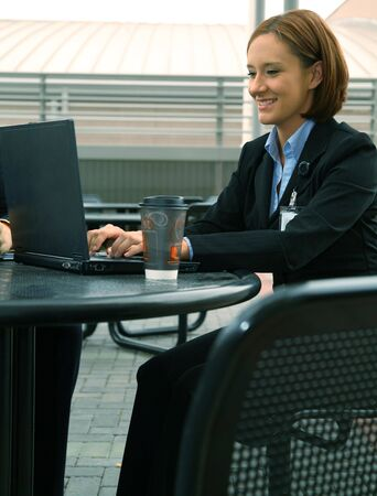 shot of business woman showing happy expression and working on her laptop