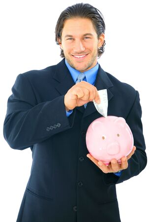 young handsome businessman inserting money into piggy bank photo