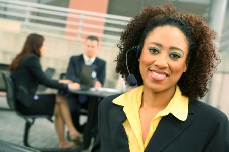 アフリカ系アメリカ人ビジネス女性 wiearing ヘッドセットと彼女の同僚のバック グラウンドに表示します。 写真素材