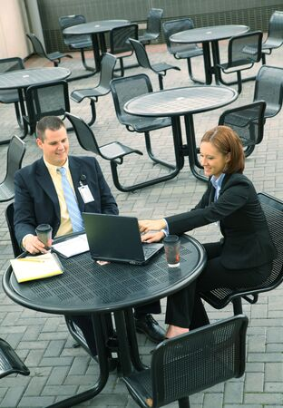 two business people discussing business outdoor with laptop on empty outdoor sitting photo