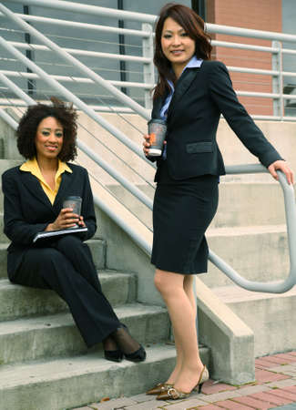 asian business women: african american and asian business women are talking by stair