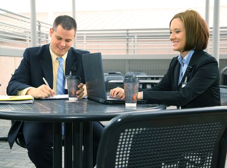 two business people discussing business outdoor with laptop on outdoor sitting photo