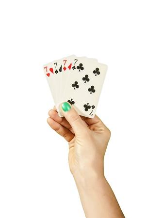 jack pot: Una mano que sostiene cuatro siete de la suerte sobre blanco Foto de archivo