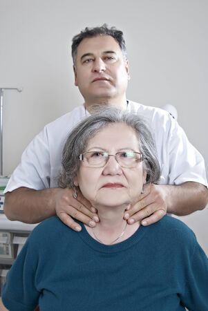 Doctor examing thyroid of mature patient photo