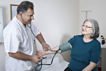 Doctor measuring mature patient blood presure photo