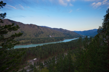 katun: The river flows between the mountains covered with forest on the Altai at sunset