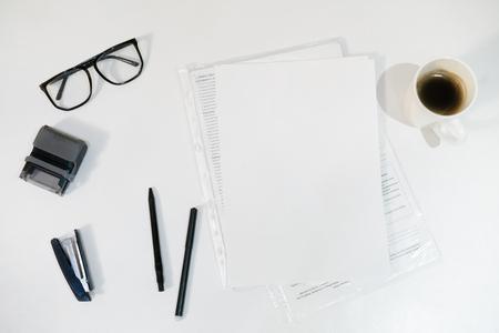 paper, pens, stapler and glasses on a white background. office white table. 版權商用圖片