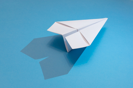 white paper plane with shadow on a blue paper background