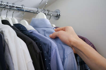 A man's hand takes a shirt on a hanger from a closet.