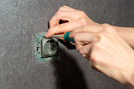 Male hands screw electronic socket on the wall.