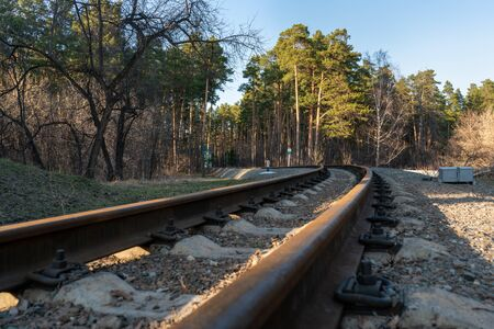 Railway rails close-up on the background of the forest and road with cars.