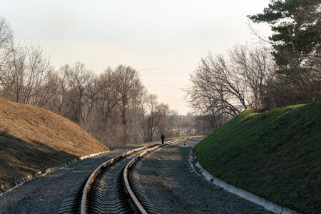 One boy child goes into the distance in the middle of the railway.