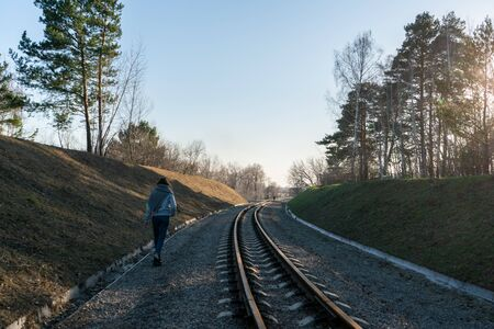 The girl alone goes along the railroad rails against the backdrop of the sunny sky.