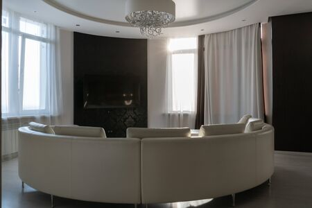 Modern black and white interior. Semicircular leather sofa against the window. Banco de Imagens