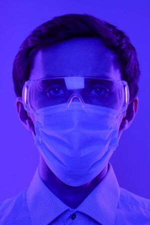 Doctor or scientist with glasses and a medical mask. Portrait in a dramatic blue-violet neon light.