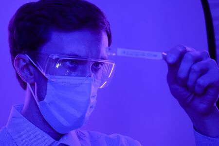 The doctor in glasses and a medical mask looks at the temperature on a thermometer. Portrait in a blue-violet neon light. Banco de Imagens