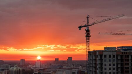 Crane and construction site on the background of the city and a beautiful orange sunset.