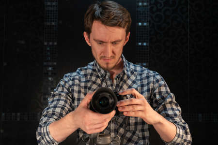 Portrait of a photographer with a camera on a dark background.