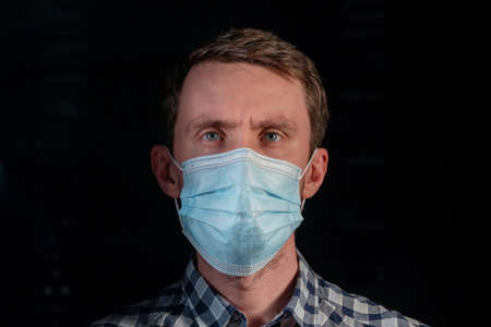 Portrait of a man in a medical mask on a dark background.