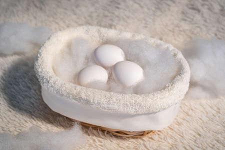 Three white eggs in a basket. Banco de Imagens