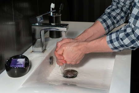 Washes his hands under the tap in the sink closeup.