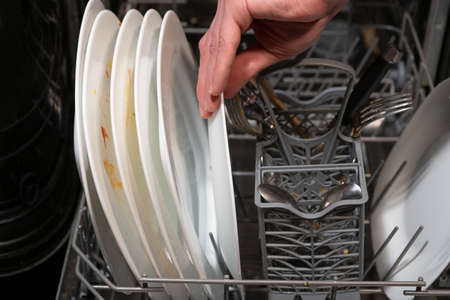 Places the dishes in the dishwasher.