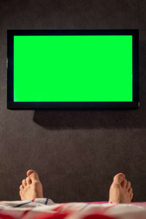 Green screen TV in front of the bed. Feet in the frame. Banco de Imagens
