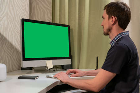 A man works in front of a computer with a green screen. Banco de Imagens
