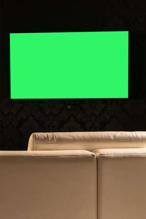 Green TV screen on the background of the sofa close-up.