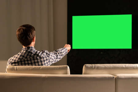 A man watches TV with a green screen while sitting on the couch. Banco de Imagens