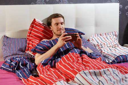 A man with a smartphone lying in bed.