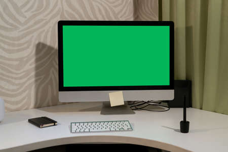 A computer with a green screen stands on the table. Banco de Imagens