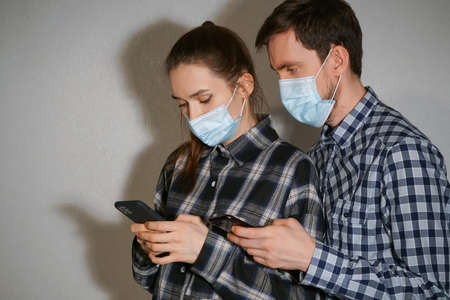A man and a girl in masks stand side by side and use smartphones.