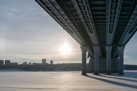 Bridge bottom view in winter. Metal structures and columns against the sky.