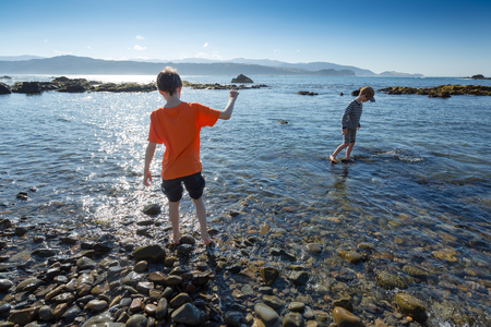 7 9 years: Boy with dark hair and orange shirt (9 years), and boy with cap (7 years) paddle in the sea on a bright, blue summers morning at Breaker Bay, Wellington, New Zealand.jpg Stock Photo