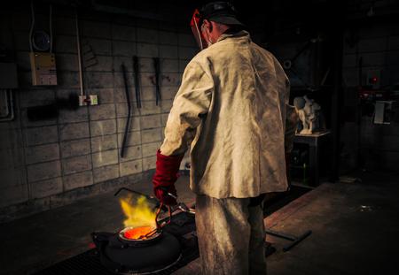 crucible: Mature man checks heat of crucible for hot metal bronze pour, using plaster moulds. An art school class in Wellington, New Zealand.