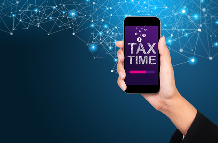 Tax time concept. Tax time on smartphone screen in businesswoman hand.