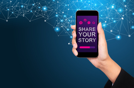 Share your story concept. Share your story on smartphone screen in businesswoman hand.