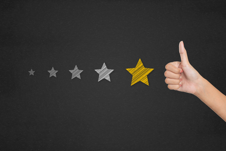 Customer satisfaction survey concept. Thumb up pointing at positive five star feedback.