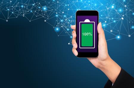 Icône verte de batterie complètement chargée sur un écran de téléphone portable. Femme le tenant dans la main.
