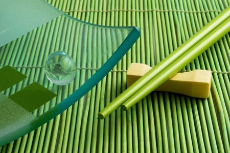 Bamboo rug, a dish and chopsticks for a sushi. photo