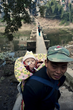 Sichuan Province, China 2 February: Sichuan rural areas, a man of anonymity, carrying his child, which is the local customs, Sichuan, China, February 2, 2011 Stock Photo - 12768771