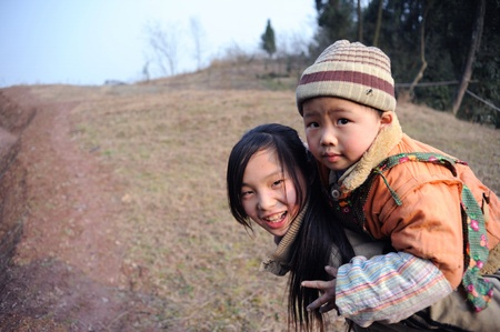 anonymity: Sichuan, China 2 February: a rural anonymity girl carrying her younger brother, in the mountain home, shot in China, Sichuan, Otake, February 2, 2011