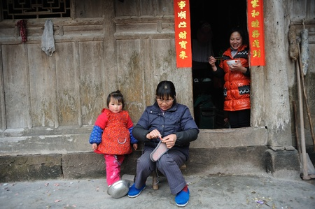 Sichuan, China - February 2: rural woman holding a child at home, February 2, 2011, the Spring Festival, a Chinese rural woman and her children standing in front of her house smiling, red couplets on the door close